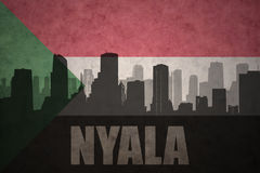Abstract silhouette of the city with text Nyala at the vintage sudanese flag. Background Royalty Free Stock Photo