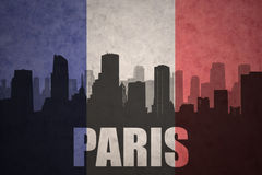 Abstract silhouette of the city with text Paris at the vintage french flag Royalty Free Stock Images
