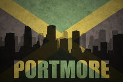 Abstract silhouette of the city with text Portmore at the vintage jamaican flag. Background stock photo