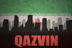 Abstract silhouette of the city with text Qazvin at the vintage iranian flag. Background Stock Images