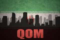Abstract silhouette of the city with text Qom at the vintage iranian flag. Background Stock Photo