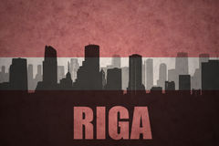 Abstract silhouette of the city with text Riga at the vintage latvian flag Stock Images
