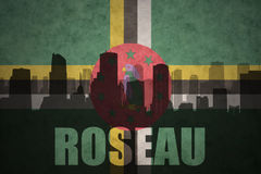 Abstract silhouette of the city with text Roseau at the vintage dominica flag Royalty Free Stock Photography