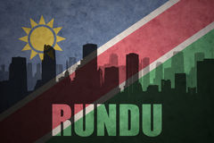 Abstract silhouette of the city with text Rundu at the vintage namibian flag. Background Royalty Free Stock Photo