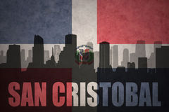 Abstract silhouette of the city with text San Cristobal at the vintage dominican republic flag Stock Photo