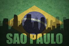 Abstract silhouette of the city with text Sao Paulo at the vintage brazilian flag. Background Royalty Free Stock Photos