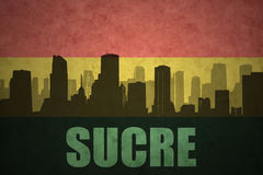 Abstract silhouette of the city with text Sucre at the vintage bolivian flag Royalty Free Stock Images