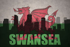 Abstract silhouette of the city with text Swansea at the vintage wales flag Royalty Free Stock Image