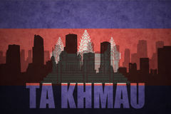 Abstract silhouette of the city with text Ta Khmau at the vintage cambodian flag. Background Royalty Free Stock Photo