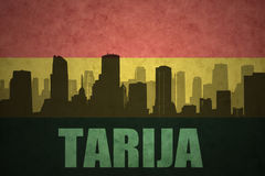 Abstract silhouette of the city with text Tarija at the vintage bolivian flag Stock Images