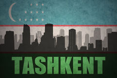 Abstract silhouette of the city with text Tashkent at the vintage uzbekistan flag. Background royalty free stock images