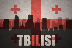Abstract silhouette of the city with text Tbilisi at the vintage georgian flag Stock Images