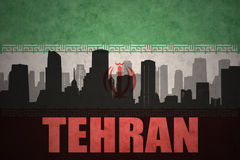 Abstract silhouette of the city with text Tehran at the vintage iranian flag. Background Royalty Free Stock Images
