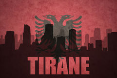 Abstract silhouette of the city with text Tirane at the vintage albanian flag Royalty Free Stock Image