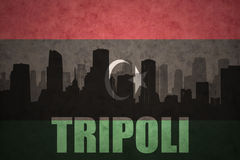 Abstract silhouette of the city with text Tripoli at the vintage libyan flag Royalty Free Stock Images
