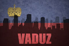 Abstract silhouette of the city with text vaduz at the vintage liechtenstein flag Royalty Free Stock Image