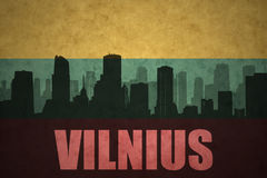 Abstract silhouette of the city with text Vilnius at the vintage lithuanian flag Stock Photos