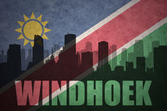 Abstract silhouette of the city with text Windhoek at the vintage namibian flag. Background Stock Photo