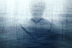 Abstract silhouette of man with heart symbol. Blurry silhouette of a man on blue rainy window with hand drawn heart symbol. Selective focus used royalty free stock image