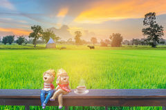 Abstract silhouette soft blurred and soft focus of sunset with the boy and girl cartoons dolly on the wooden seat,cup of coffee, g. Reen paddy rice field, the Stock Photos