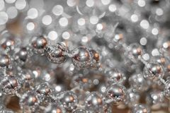 Abstract silver christmas background. Thread with beads with golden glare and beautiful bokeh. Abstract silver christmas background with soft focus. Thread with Royalty Free Stock Images