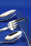 Abstract silverware. Silver cutlery arranged in abstract fashion against a blue background Stock Image