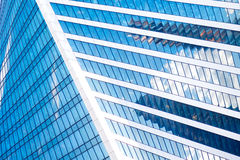 Abstract skyscrapers with reflection in windows blue sky, white clouds and sun glare Stock Photo