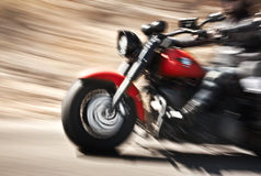 Abstract slow motion, biker riding motorbike. Driver racing on the big red bike, side view, blur movement, summer road trip, speed concept royalty free stock image