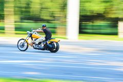 Abstract slow motion, biker riding yellow motorbike. Abstract Motion Blur, Biker Riding Motorbike, Driver Racing on the Big Yellow Bike, Side View, Blur Movement Royalty Free Stock Photos
