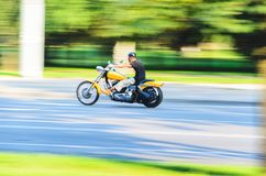 Abstract slow motion, biker riding yellow motorbike. Abstract Motion Blur, Biker Riding Motorbike, Driver Racing on the Big Yellow Bike, Side View, Blur Movement Stock Photography