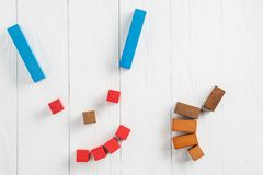Abstract smiling face from multi-colored wooden blocks with hand thumb up. Positive concept royalty free stock photo