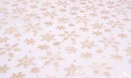 Abstract snowflake background. A background of light, golden illustrated snowflakes on a white background Stock Photos