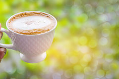 Abstract soft blurred and soft focus a cup of cappuccino,mocha,coffee with the with the bokeh,beam light ,lens flare effect tone a. Nd copy space background Royalty Free Stock Photo