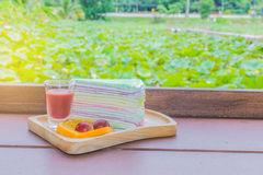 Abstract soft focus cocoa, coffee, rainbow crepe, lemon, grape, on the wooden tray with blurred the lotus plant field, beam light,. Lens flare effect tone Stock Photos