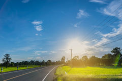Abstract soft focus semi silhouette the road, green paddy rice field with the beautiful sky and cloud in the afternoon Thailand, t. He beam, light, and lens Stock Image