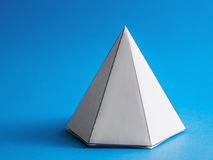Abstract solid pyramid shape. Closeup of an abstract solid pyramid shape with a blue background royalty free stock photo