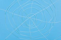 Abstract spiderweb, white threads blue background. Royalty Free Stock Images