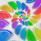 Abstract spiral fruit jelly rainbow wedges slices on white sugar sand background. Rainbow jelly candies. Sweet fruit jelly liths. Candy dessert. Abstract food Royalty Free Stock Photos