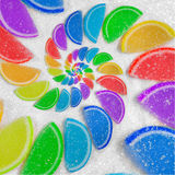 Abstract spiral fruit jelly rainbow wedges slices on white sugar sand background. Rainbow jelly candies. Sweet fruit jelly liths. Candy dessert. Abstract food Stock Image