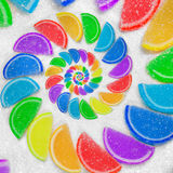 Abstract spiral fruit jelly rainbow wedges slices on white sugar sand background. Rainbow jelly candies. Sweet fruit jelly liths. Candy dessert. Abstract food Royalty Free Stock Photography