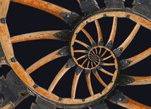 Abstract spiral wooden wagon cannon wheel with black metal brackets, rivets. Wheel wooden rim spokes background. Horse vehicle whe Stock Photo