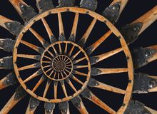 Abstract spiral wooden wagon cannon wheel black metal brackets rivets. Wheel wooden spokes fractal background. Horse vehicle wheel Stock Images