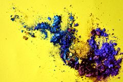 Abstract splash of blue and purple powder on yellow background stock photo