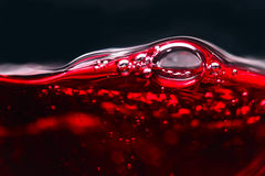 Abstract splashes of red wine on a black background Stock Photo