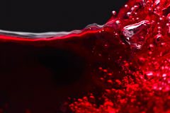 Abstract splashes of red wine on a black background Stock Images