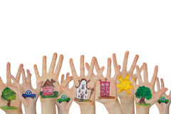 Abstract street made of painted symbols. Houses, trees, cars painted on children hands raised up. Royalty Free Stock Photo