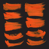 Abstract strokes drawn thick orange paint on black pap Stock Images
