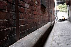 Abstract style photograph looking down a brick lined alley way with cobblestones royalty free stock photo