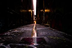 Abstract style photograph looking down a graffiti lined alley way stock photo