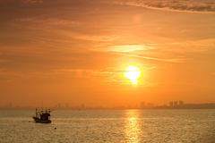 Abstract sunrise in the sea view of sea ship near the town at as Royalty Free Stock Image